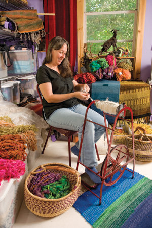 Lisa spinning yarn in the middle of her workshop