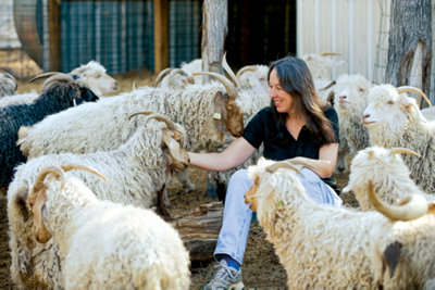 Lisa sitting on the ground in the middle of the herd giving her goats some one-on-one affection