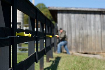 Man setting up an electric livestock fence.