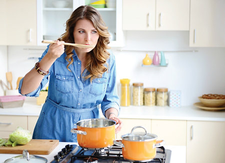 woman taste-testing with a wooden spoon while she cooks