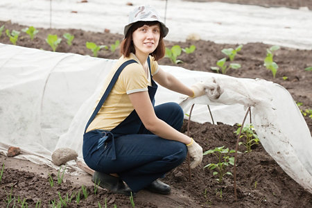 woman in overalls, hat, and gloves working on a hoop house