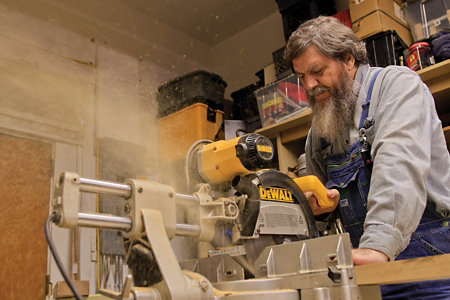 George using a circular saw to cut a board