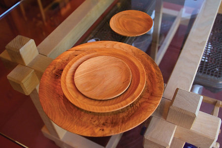 some wooden plates made by George sitting on a glass table