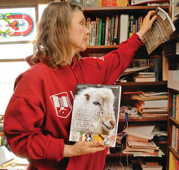 Deborah with 'Raising Goats Naturally' in her arms and pulling another book off the full bookshelf