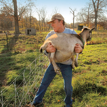 Mike next to a fence with a goat in his arms