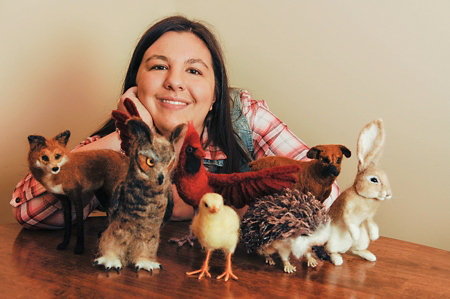 Megan with some of her felted wool animals - fox, owl, chick, hedgehog, and rabbit