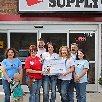 Heart of Phoenix receives the prize check from their local Tractor Supply store.