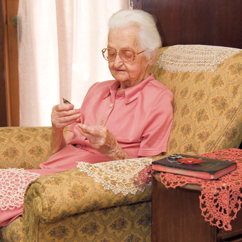 Ama Lou tatting in a comfortable chair with several pieces of completed lace laid around her