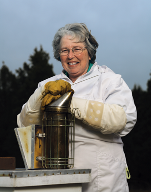 Shirley DeBusk in her beekeeping suit next to a beehive