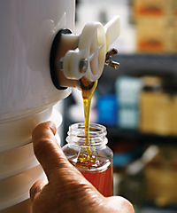 filling a honey jar from a spigot