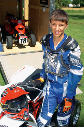 Christian with all his gear standing next to his ATV