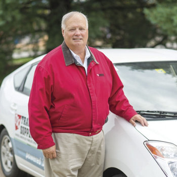 Dr. Cliff Ricketts next to his alternative fuel car