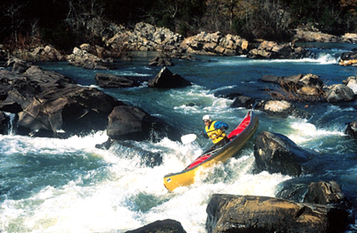 man canoeing through some rapids on the Cossatot River