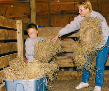 Kim and her son Gabriel working with the hay