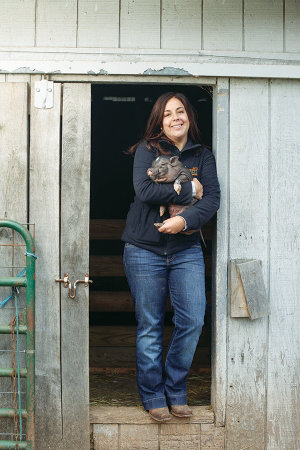 Janel holding a pig in her arms
