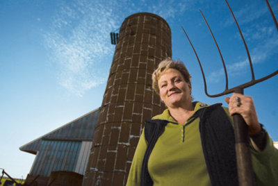 Connie Snyder, pitchfork in hand, standing in front of her silo