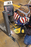 man in safety equipment using an arc welder