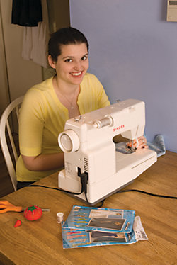 girl sitting behind her sewing machine, working