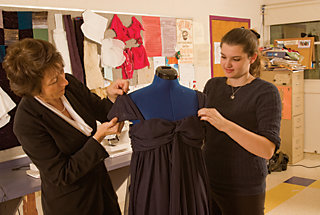 Maribeth Courtney and Olivia Newcomb arranging a dress on a mannequin