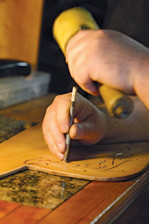Kevin using a couple of his tools to etch artwork into a piece of leather