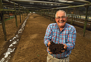Jack Brantley holding a handful of worms and dirt