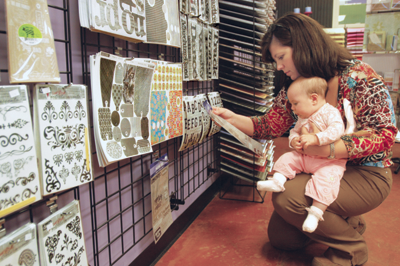 Scarlett Kelley with baby Brooke browsing a craft store