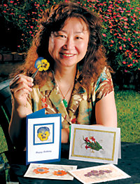 Kate Chu sitting behind a couple of handmade cards