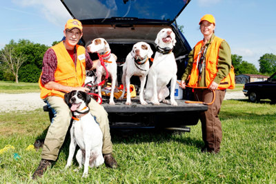 Steve and Chris Selep with their four dogs on the back end of a truck