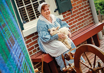 Tracy in period clothing with a lamb on her lap, a spinning wheel in the foreground