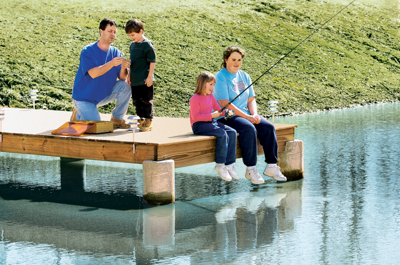 the Holland family on the dock at their pond