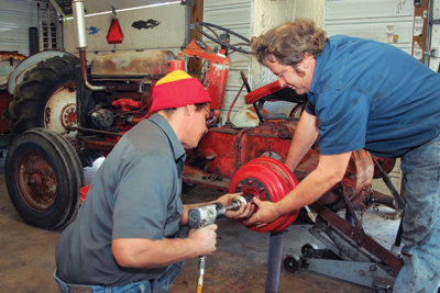 Laughlin and his dad repairing a tractor together