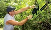 Chris Mays, of Cedar Hill, TN, using a chainsaw