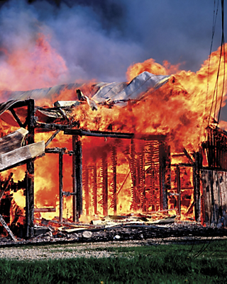 a burning barn engulfed in flames, only the frame and the metal roof of the structure is left
