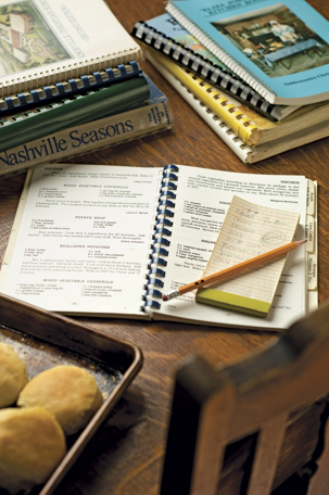 cookbooks laying on a desk with one open and a notepad and pencil on top