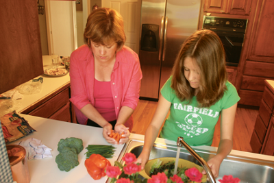 Mary and Emily preparing dinner for four families