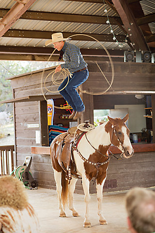 Kevin jumping through a rope on the back of his horse