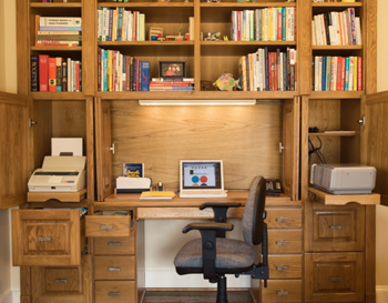 a desk with surrounding shelves and cabinets