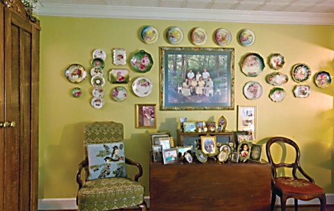 hand-painted china surrounding family photos on the wall