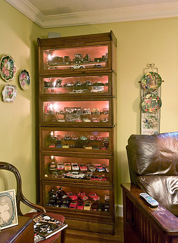 die-cast cars in an illuminated cabinet
