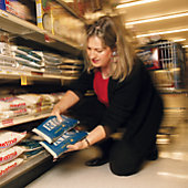 woman kneeling to check unit prices on rice
