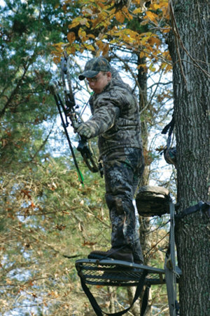 hunter in a tree stand aiming an arrow