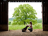 Little girl with a dog in a barn