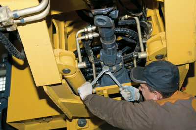 man working on a tractor engine