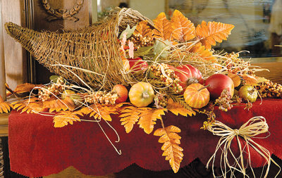 a basket as an autumn nest lined with straw or dried grasses, with small pumpkins, gourds, fallen leaves, and nuts tucked in