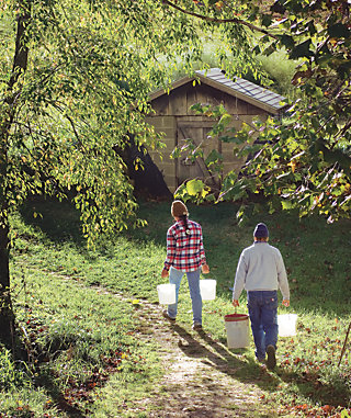 Liz and Jeff Padgett walking along a dirt path on their farm carrying empty buckets