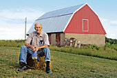 man sitting on a hay bale with a barn in the background