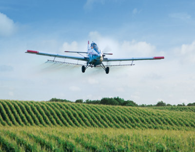 plane flying over some crops spraying product