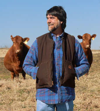 Teddy Gentry with his cattle in the background