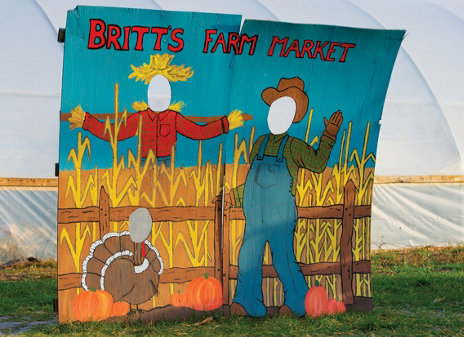 a painted farmer's family on a wooden board with face cutouts for photo ops