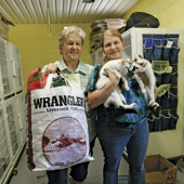 Doris Winstead (right) with two rescued cats and Judy Ingle with one of their created shopping bags